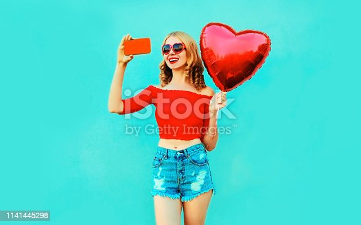 istock Beautiful smiling young woman taking selfie picture by phone with red heart shaped air balloon wearing shorts on colorful blue background 1141445298