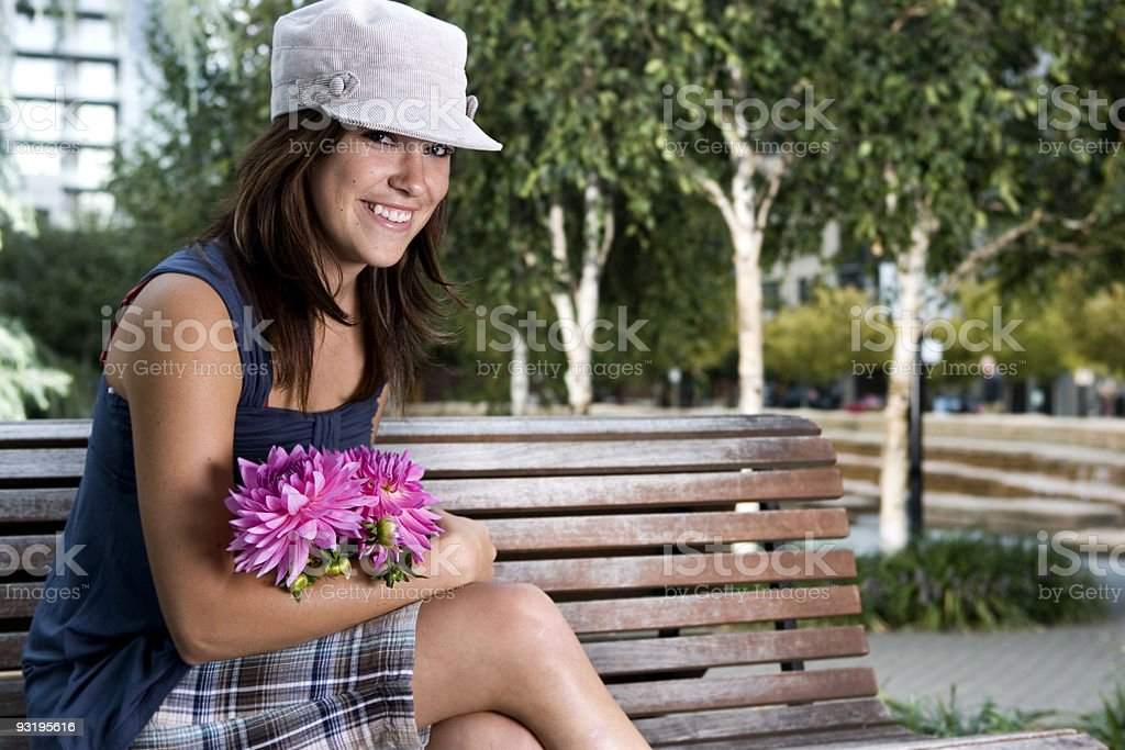 Beautiful Smiling Young Woman with Flower Bunch on Park Bench stock photo