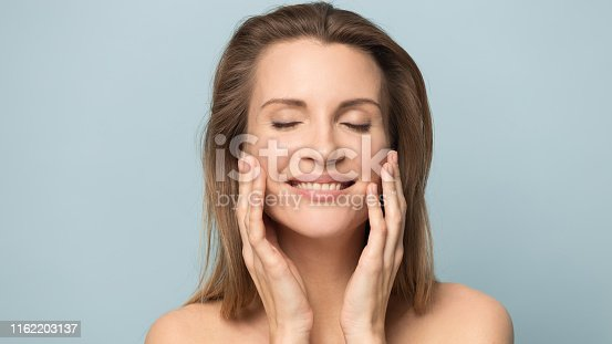 Beautiful smiling young woman with perfect skin touching face with hands, attractive female with closed eyes close up, wide image, natural beauty concept, isolated on grey studio background