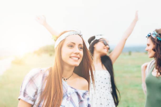 schönen lächeln junge frauen tanzen in der grassland - hippie stirnbänder stock-fotos und bilder
