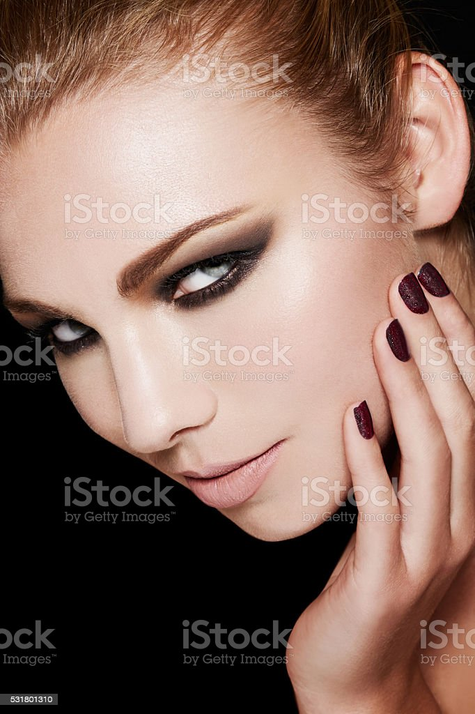 Beautiful smokey eyes makeup with black manicured nails. stock photo