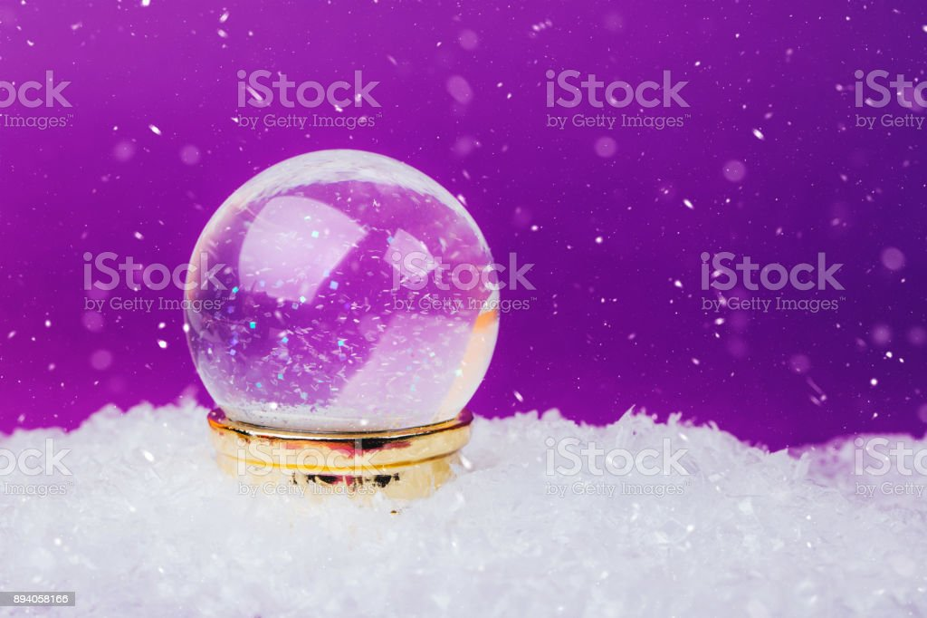 Beautiful snow ball on snowy background over Ultra Violet backdrop.