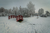 beautiful snow-covered city park. a footpath and a small picturesque wooden bridge under snow on a cloudy day