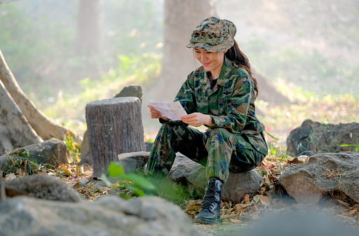 istock Beautiful soldier read the letter with happy emotion in the border line of battle field 1216221243
