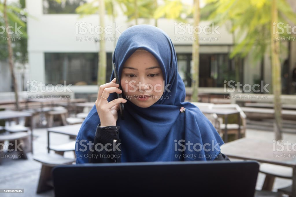 41e2eaaad Beautiful southeast asian hijab woman working on laptop and answering phone  at outdoors cafe - Stock image .
