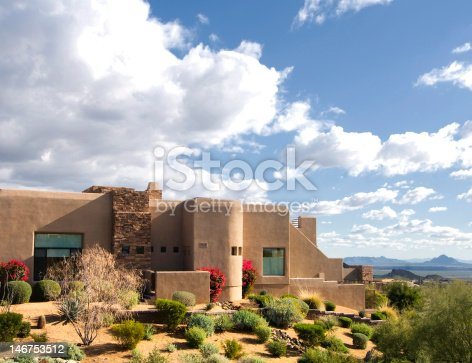 Beautiful Southwestern adobe style home located on a mountain with views of desert wilderness and mountains.