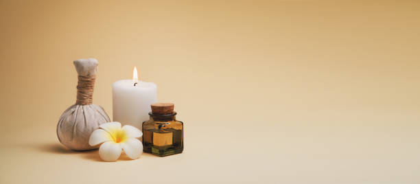 Beautiful spa composition with candle, frangipani flower, oil flask and herbal ball on beige background. Stylized warm colors and contrast. Copy space stock photo