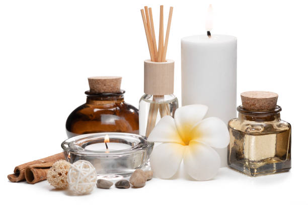 Beautiful spa composition with candles, frangipani flower, oil flasks and other decor elements. stock photo