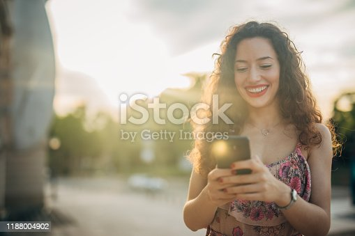 One woman, beautiful young Spanish lady using mobile phone outdoors in sunset.