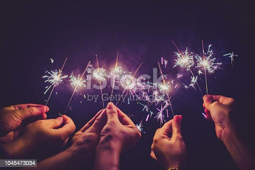 istock Beautiful sparklers in people hands on black background,holiday and xmas and new year concept. 1045473034
