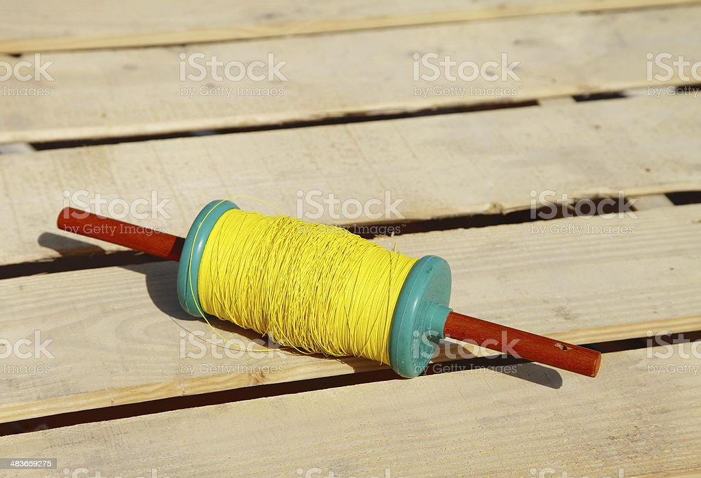Beautiful spindles with yellow thread to fly kites stock photo