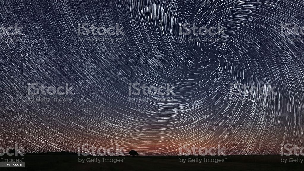 Beautiful Spiral Star Trails over filed with lonely tree. stock photo