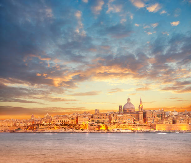 Beautiful spires and cathedral dome of Valletta under dramatic sky on the sunset stock photo