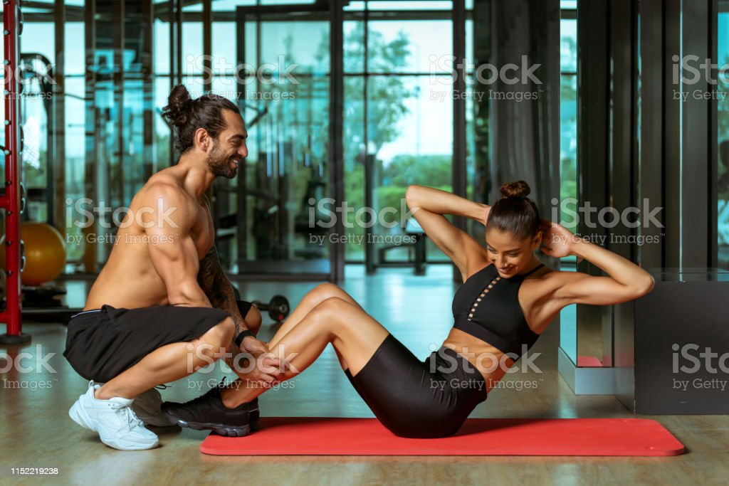 Beautiful sport woman exercise doing sit ups with personal trainer in...