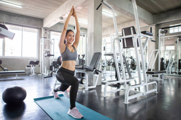 beautiful sport young asian woman in sportswear stretching muscle legs and up hands  on mat in fitness gym. workout . training.  exercising . healthy lifestyle. warm up and cool down morning light stock photo