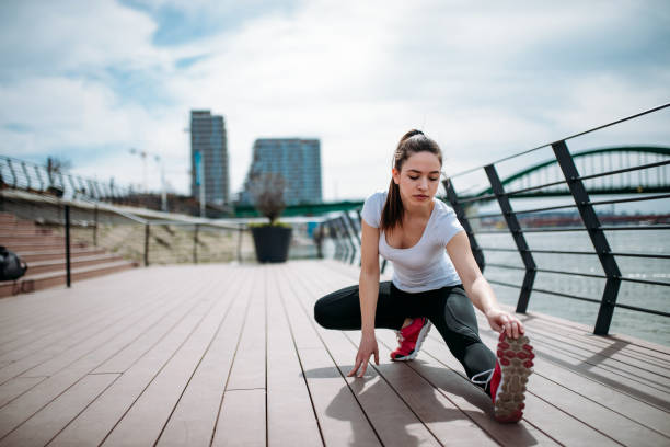 Beautiful sportswoman doing streching exercises outdoors. stock photo