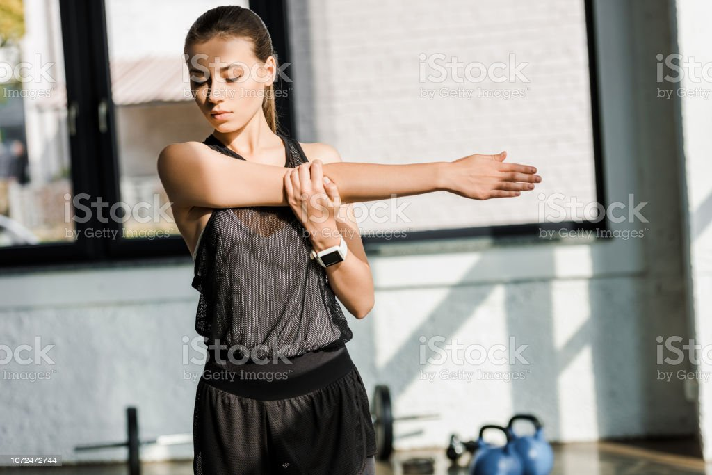 beautiful sportswoman doing stretching exercise before training session at gym