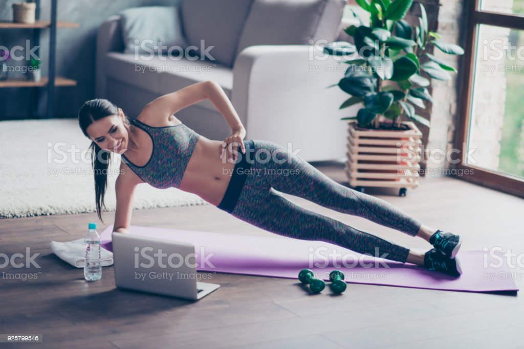 Beautiful sporty cheerful woman is doing side plank exercise. She is watching video on the internet and repeating the tasks - Zbiór zdjęć royalty-free (Aerobik)