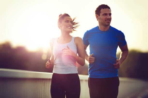 Beautiful sporty couple running and jogging outdoors stock photo