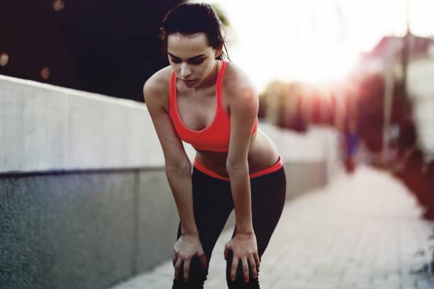 schöne sportliche joggerin müde nach dem laufen - gewicht schnell verlieren stock-fotos und bilder