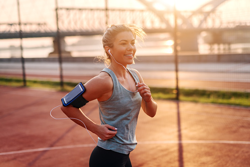 Beautiful sporty fit blond girl listening to the music and running early in the morning outside.