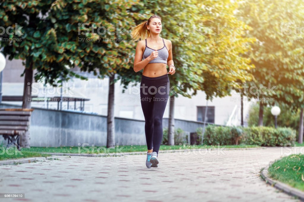 A beautiful sporty woman runing in the park in sportswear. Training sun day stock photo