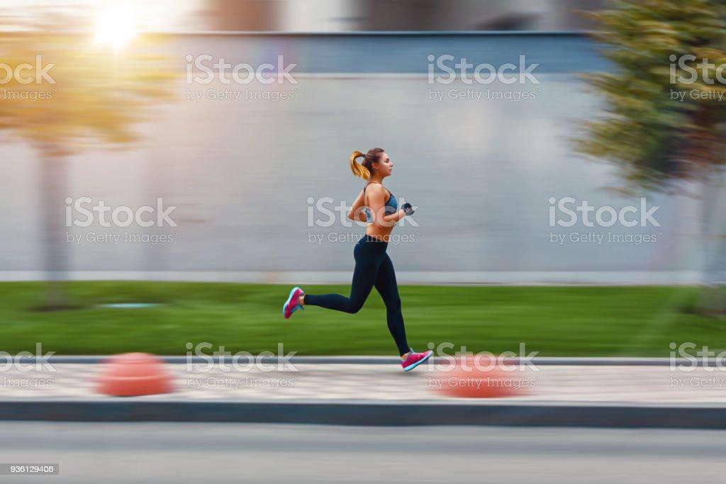 A beautiful sporty woman runing on street in sportswear. Training sun day. Big gray wall behind stock photo