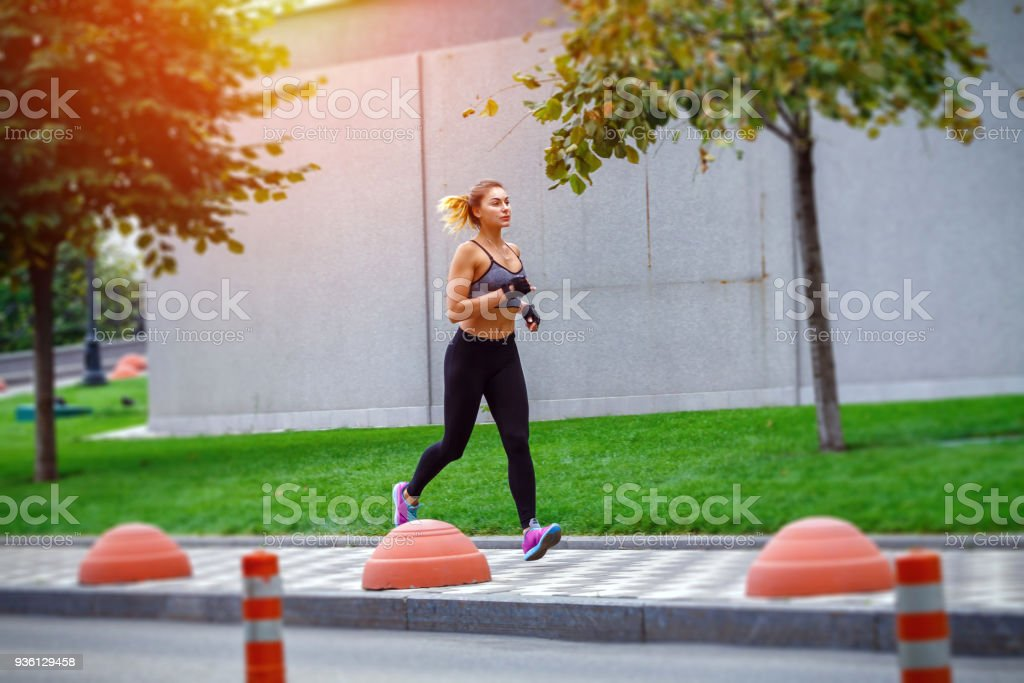 A beautiful sporty woman runing on street in sportswear. Training sun day stock photo