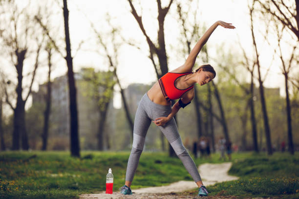 Beautiful sporty woman stretching, warming up before working out stock photo