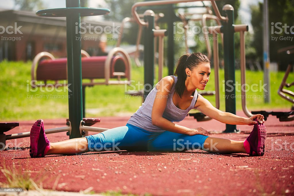 Beautiful sporty woman stretching,  warming up  before working out. royalty-free stock photo