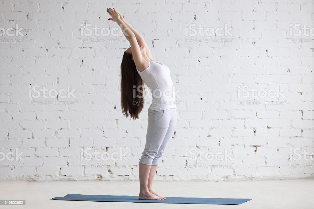 Beautiful sporty young woman doing standing backbend pose in whi stock photo
