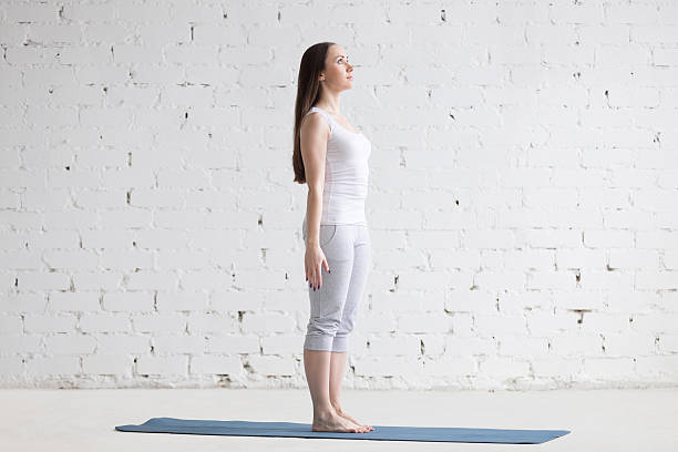 beautiful sporty young woman doing tadasana pose in white loft - poprawna postawa zdjęcia i obrazy z banku zdjęć