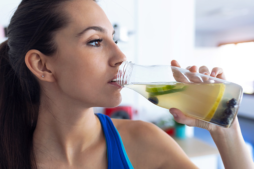 istock Beautiful sporty young woman drinking detox juice in the kitchen at home. 1180176490