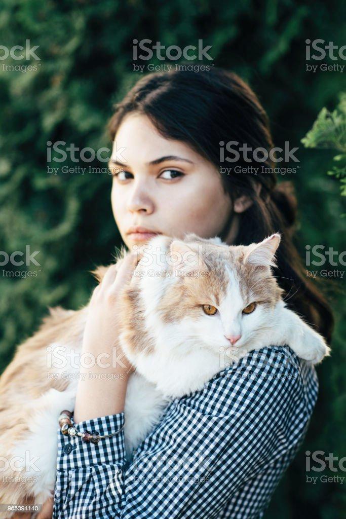 Eine schöne sitzt auf den Händen von einem hübschen Mädchen auf dem Hintergrund der grünen Büschen entdeckt - Lizenzfrei Auge Stock-Foto