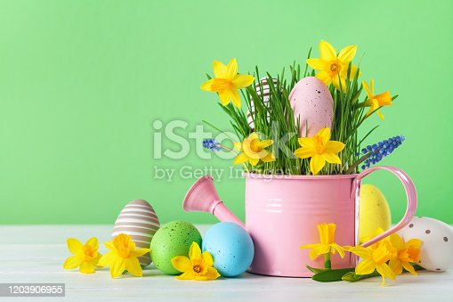 912300146 istock photo Beautiful spring composition with colorful Easter eggs, spring daffodil flowers and green grass. 1203906955