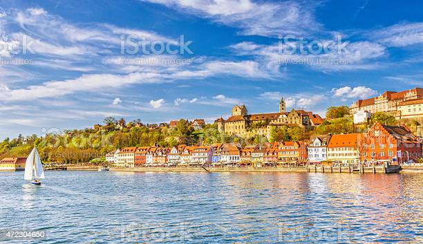 Panoramic view on the charming medieval city of Meersburg, located at the Lake Constance (Bodensee), with a sailing boat passing the city´s beautiful waterfront in the lower town and it´s landmark castles in the upper town.