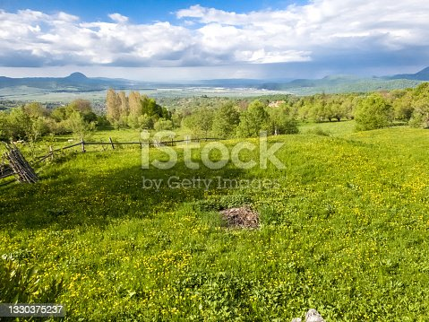 istock Beautiful  spring landscape with green field and dramatic razor sharp cloudy sky and warm sun rays 1330375237