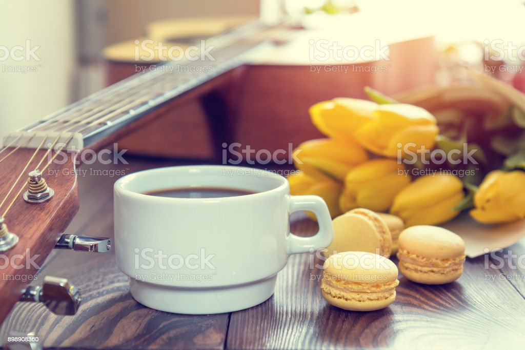 Beautiful spring music background. Cup of coffww, guitar, yellow tulips, musical page on a dark wooden background. Shallow depth of field. Coloring photo with soft focus in instagram style royalty-free stock photo