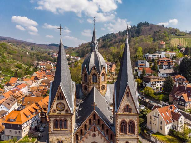 Schönes Frühlingsfoto von oben auf einer Kirche in Heppenheim Orange Hausdächer, Berge und ein blauer Himmel im Hintergrund. Deutschland. – Foto