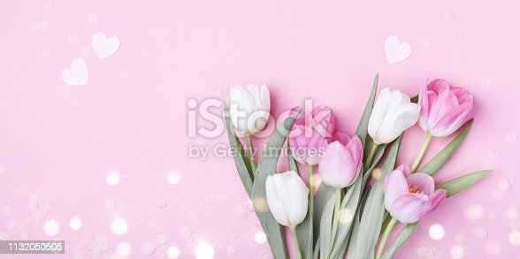 659293084 istock photo Beautiful spring tulip flowers on pastel pink table top view. Greeting banner for International Women Day, Mother day. 1132050505