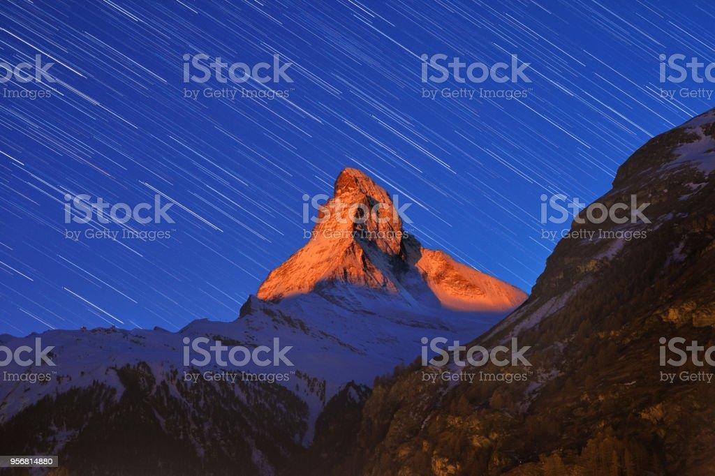 Beautiful star trails over the famous mountain Matterhorn at sunrise tine in winter, Zermatt, Switzerland. stock photo