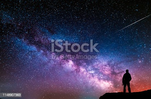 Beautiful starry night, man silhouette with a camera looking at the Milky Way galaxy.