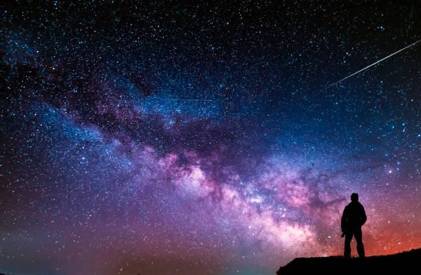 beautiful starry night, man silhouette with a camera looking at the milky way galaxy. - céu a noite imagens e fotografias de stock