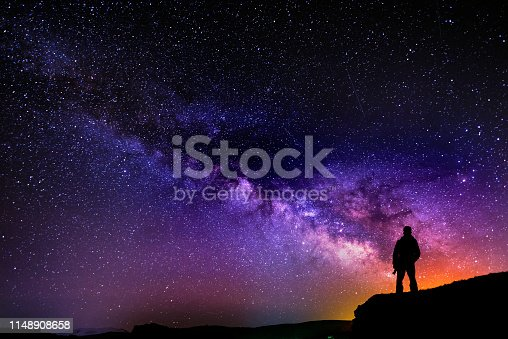 istock Beautiful starry night, man silhouette with a camera looking at the Milky Way galaxy. 1148908658