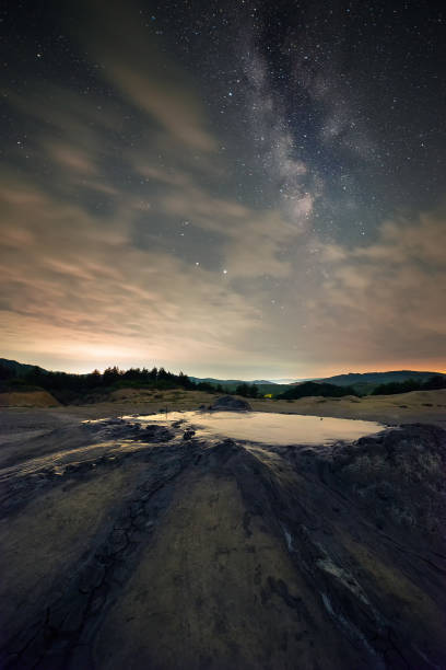 Beautiful starry sky with the Milky Way galaxy and a volcano crater in the foreground shot in Romania, Buzau County at Muddy Volcanoes Vulcanii noroiosi stock photo