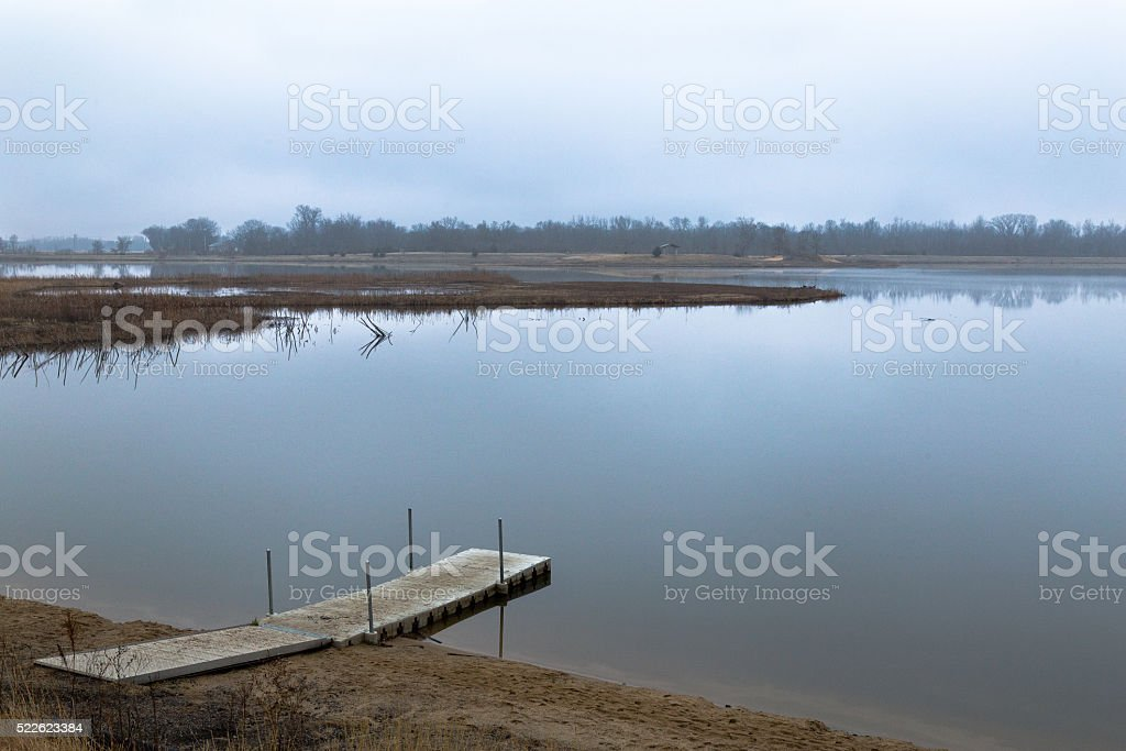 Beautiful Still Lake With Dock On Cloudy Day stock photo