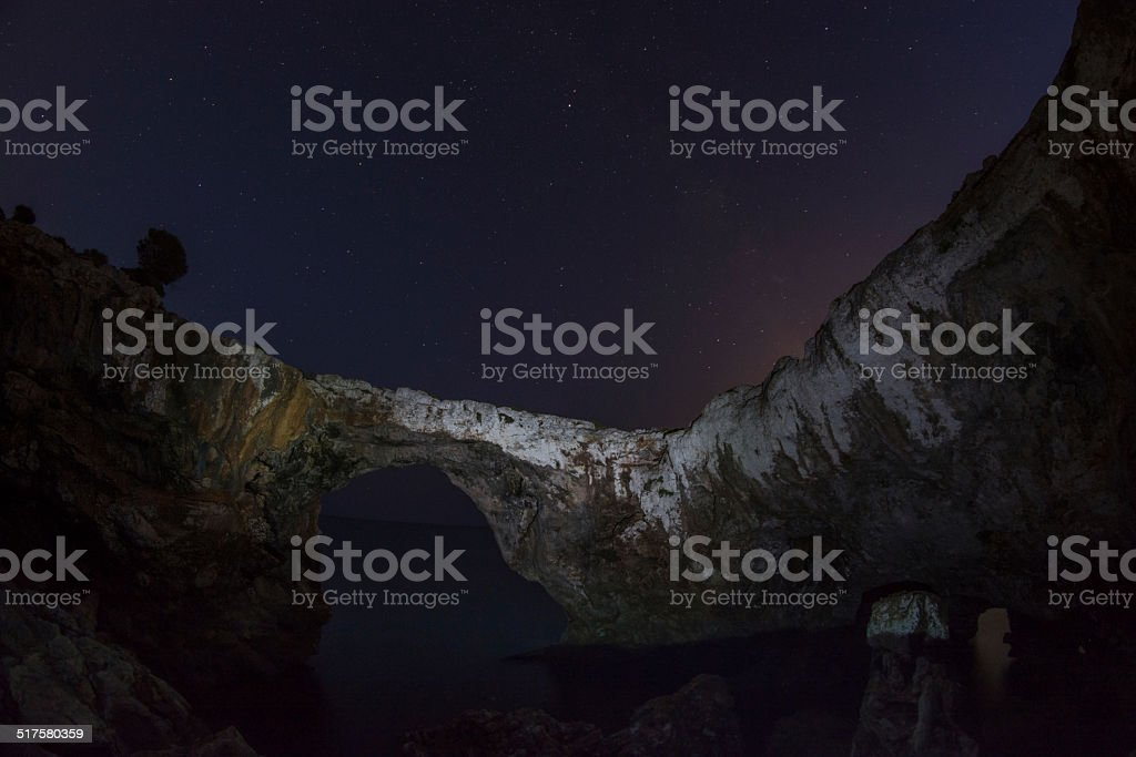 Beautiful stone arch ocean night and milky way stock photo