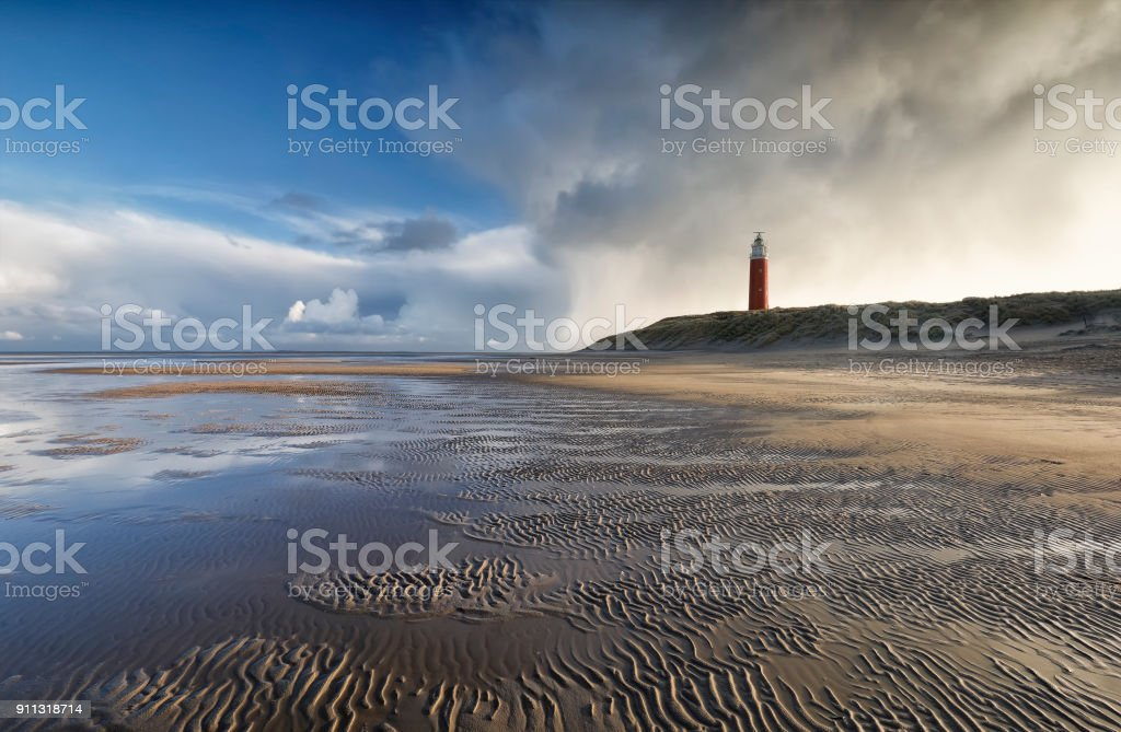beautiful stormy sky over North sea beech and lighthouse stock photo