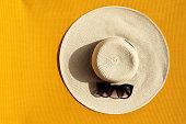 黄色の鮮やかな鮮やかな背景にサングラスと美しい麦わら帽子。平面図です。夏の旅行休暇の概念。