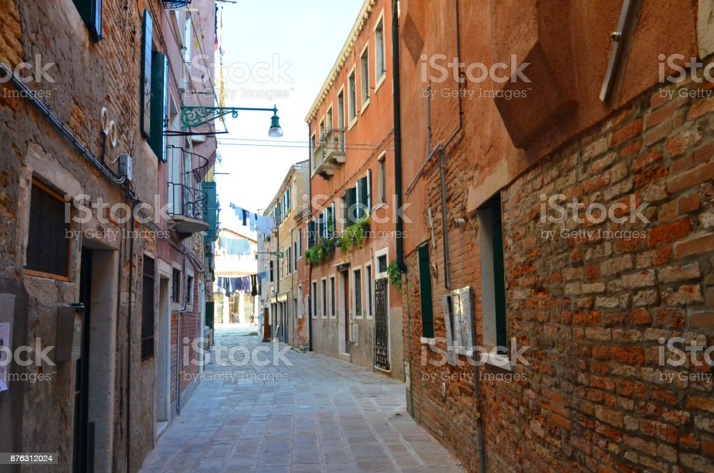 Beautiful street with brown brick buildings in Venice, Italy stock photo